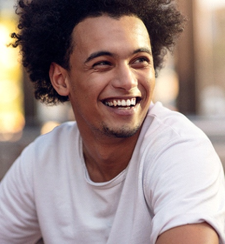 Young man in white shirt smiling with dental implants in Bettendorf, IA
