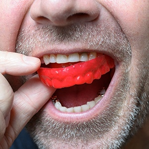Closeup of man using red mouthguard